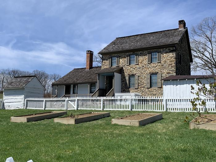 Stone and brick farmhouse with porch and picket fenced yardBushman House, east side