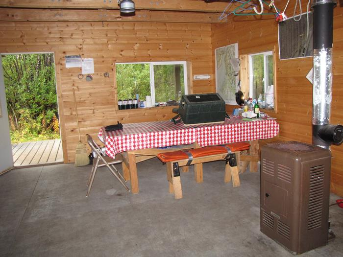 view of table and heater inside Esker Stream Cabin (Wrangell-St Elias)