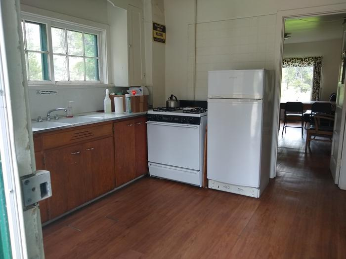 A kitchen with sink, refrigerator, propane stove, and hardwood floor.Beaver Creek Cabin's kitchen.