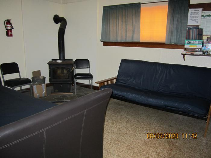 A wood stove with two futons couch-beds in a living room.Barber Flat's living room, with two futon couch-beds.