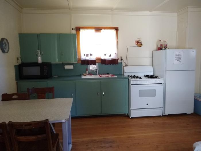 A kitchen with a table, microwave, sink, stove, and refrigerator.Another look at the kitchen at Atlanta Cabin.