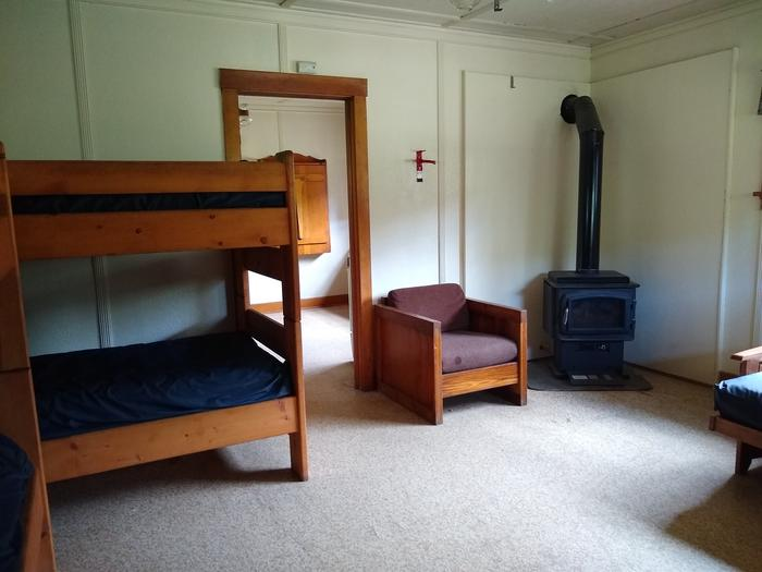 Bunk beds next to a chair and wood stove.The sleeping room features a wood stove for warmth.