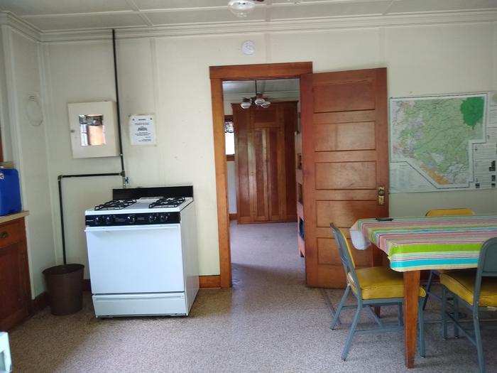 A stove next to a table with chairs and a door leading into a bedroom.Deer Park's kitchen has a stove and dining room table with chairs.