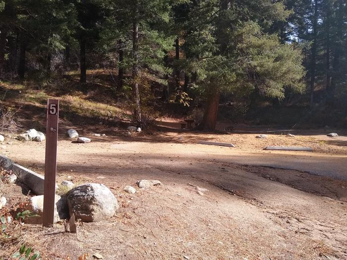 A dirt parking space with a campsite in the shaded background and a #5 post in the foreground.Spot 5 a Hayfork also features generous parking space.   Please remember that individual sites cannot be reserved.  Hayfork Group Campground can only be reserved as a whole.