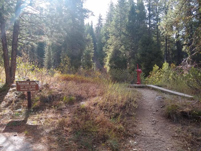 """A red water pump next to a """"Narrow Road: Not Suited for Trailers"""" sign.The water pump at Hayfork Group Campground is next to a narrow dirt path that leads to the end of the campground."""