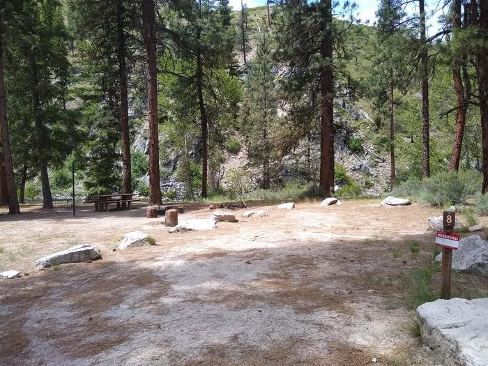 A large parking space leading up to a campsite near a river.Site 8 is wide, sunny and near the North Fork of the Boise River.
