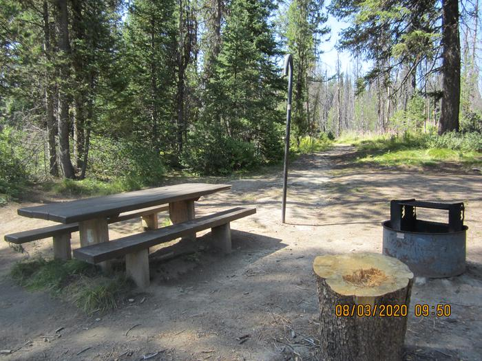 A single campsite with picnic table, fire ring, and lantern hook.A closeup of Site 7's camping area at Edna Creek Campground.