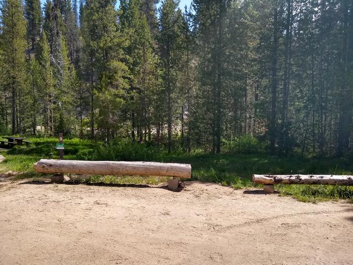 Two log parking beams next to a campsite.Site 9 features two large log parking beams.