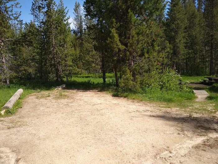 A dirt parking lot next to a small bridge leading to a campsite.A side view of Site 9's parking spot at Edna Creek Campground.  Note the bridge leading to the site.