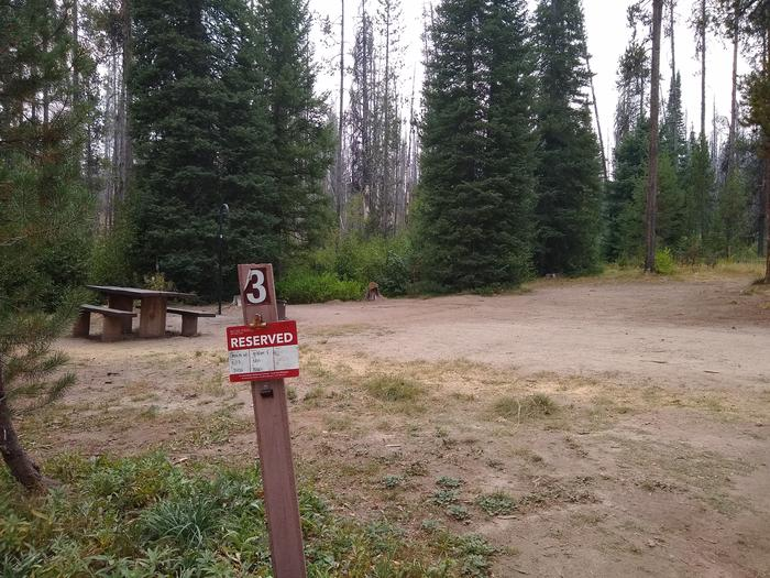 A campsite with a large dirt parking area.Site 3 has a large area for visitor use or a larger trailer.