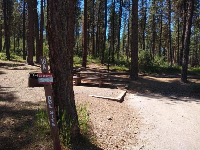"""A sign saying """"18A DBL SITE"""" at the corner of a campsite and a driveway.Site 18A is also a double site at Grayback Gulch."""