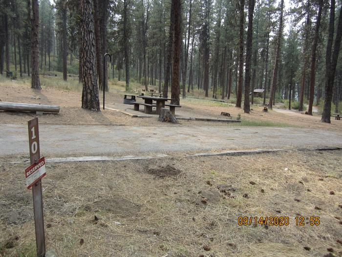 A sideways view of Site 10, with a paved driveway and the camp spot in the background.Grayback Site 10, sideways view.