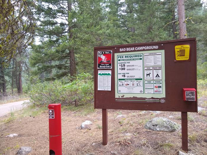Bad Bear Campground sign with payment information and fee tube.Bad Bear fees and regulation sign with fee tubes and envelopes.