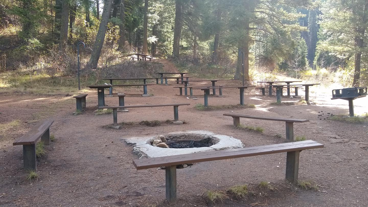 An in-ground fire pit surrounded by benches.Hayfork Group Campground Fire Pit.
