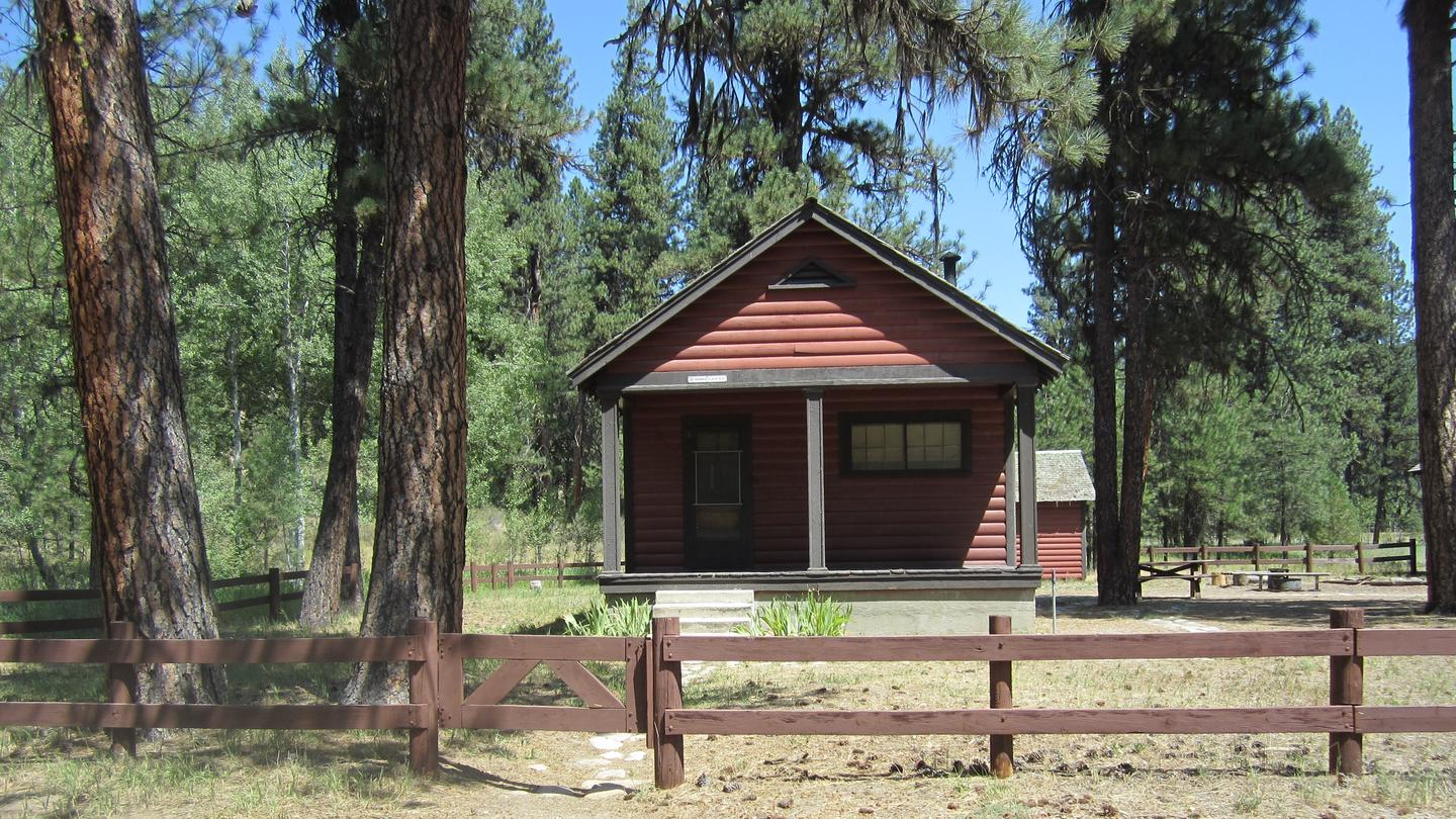 The front of a cabin with a wooden fence.Barber Flat Cabin