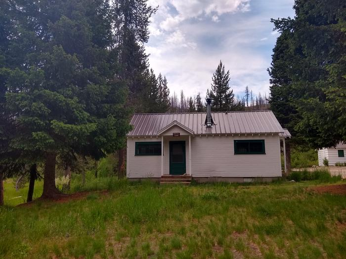 A sideways view of a white cabin in the woods.Beaver Creek Cabin