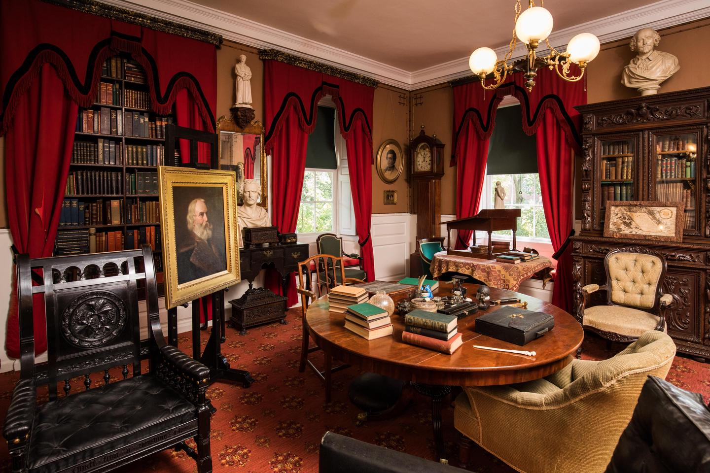 """Henry Wadsworth Longfellow's StudyThe Longfellow study table is cluttered with books and writing implements. The black """"Chestnut Tree Chair"""" was a gift to Henry Longfellow in honor of his poem, """"The Village Blacksmith."""""""