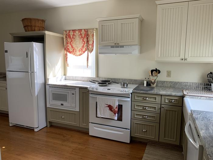Kitchen area with refrigerator, oven and stove, and sinkKitchen