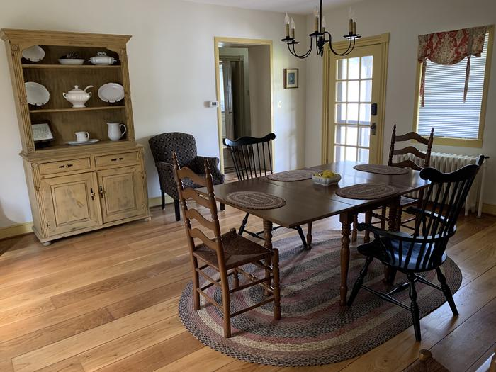Room with wood floors, dining table and six chairs and hutch with decorative platesDining Room