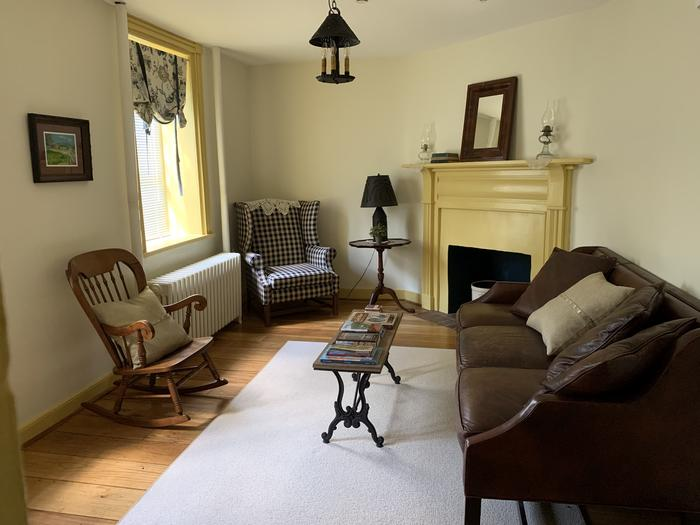 Room with fireplace, sofa, rocking chair and stuffed chairSitting Room