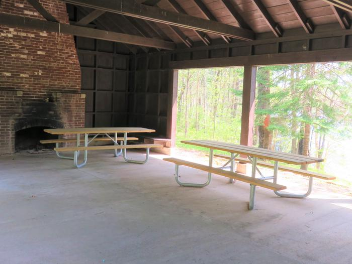 Spearhead Point shelter from insideView of some picnic tables and one fireplace inside the Picnic Point Shelter