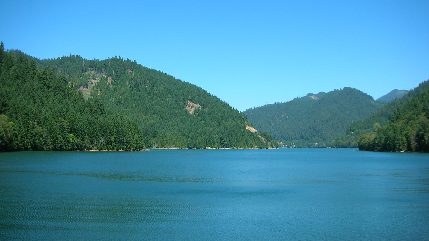 Lake with trees and hills in the backgroundView of Blue River Lake from Saddle Dam