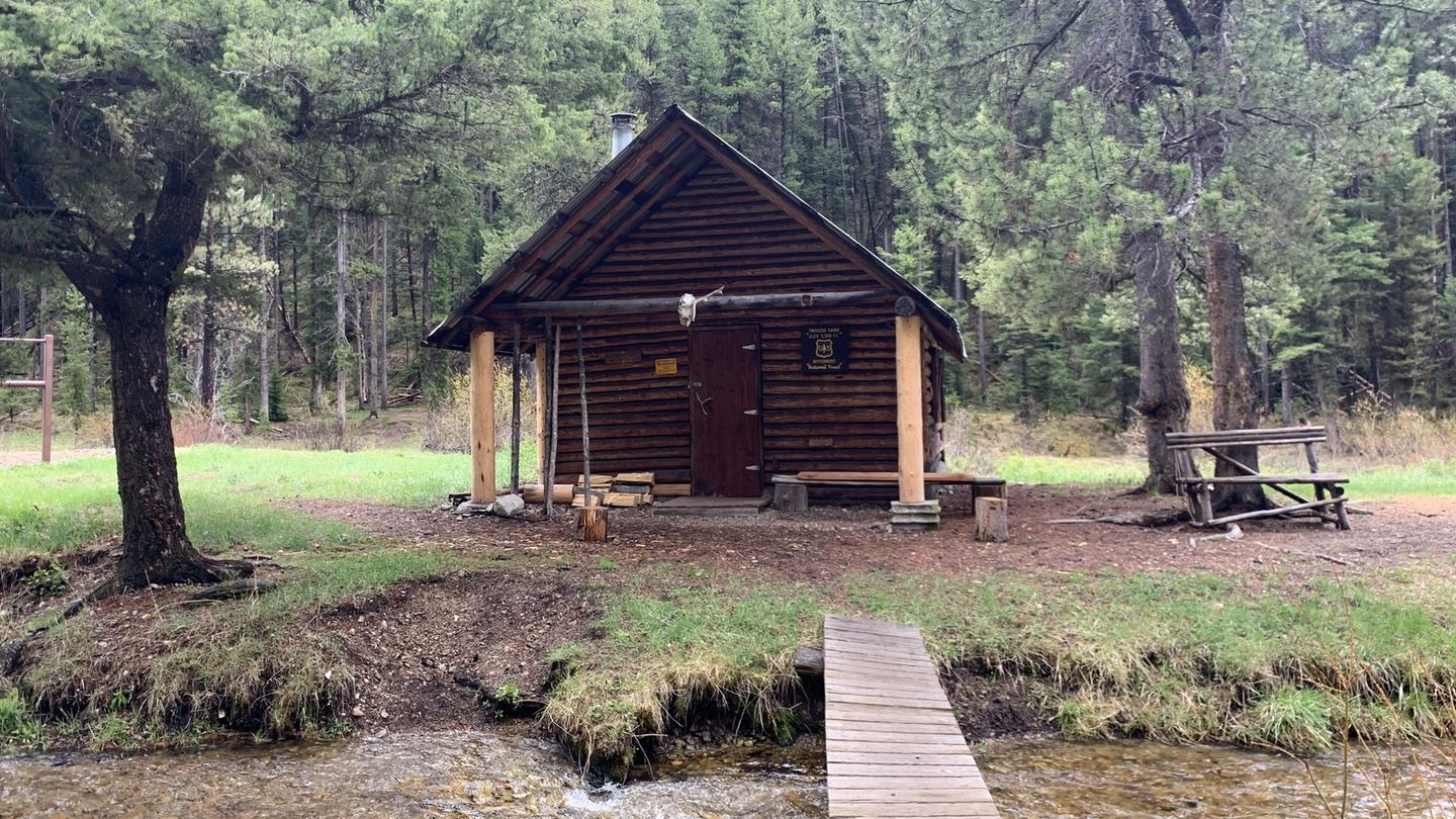 Outside Front of Twogood CabinA cabin sets near a creek in a beautiful backcountry setting with a foot bridge over the creek.