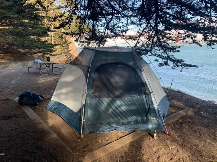 A two person tent is set up in a tent pad near a picnic table with the Golden Gate Bridge in the background.A tent at the uppermost tent pad at Site 1.