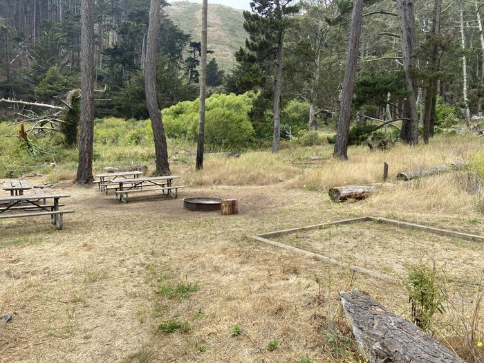 Campground with three picnic tables, a fire ring, and tent pads.Site 3 in July