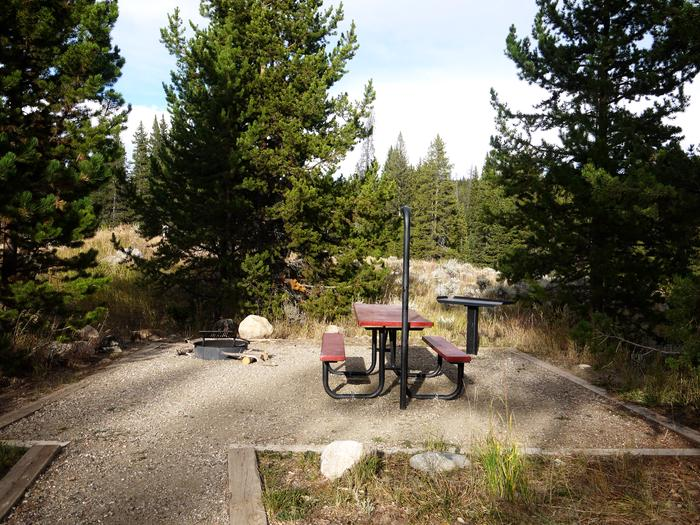 Picnic table, fire ring and grill set in the middle of a pine forest.Campsite at Boulder Park
