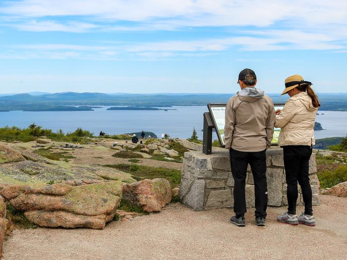 A man and woman dressed in light coats and dark pants with hats stand next to each other in front of an interpretive panel overlooking the ocean and distant mountains from the top of a mountain.Interpretive display at the Cadillac Summit.
