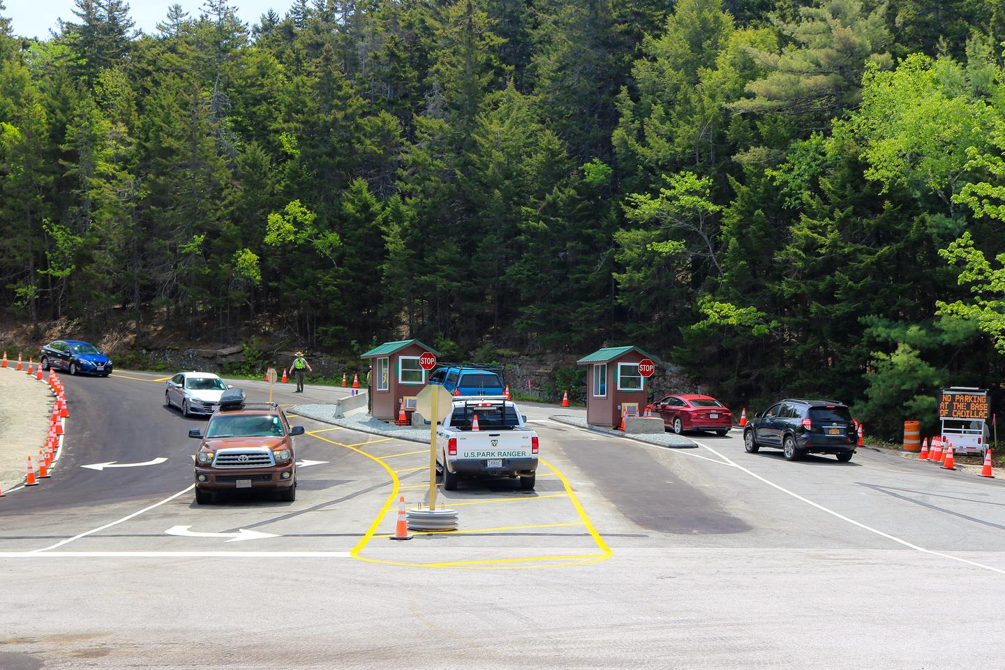 Cars enter and exit the start of a road with two entrance booths.Cadillac Summit Road entrance station.