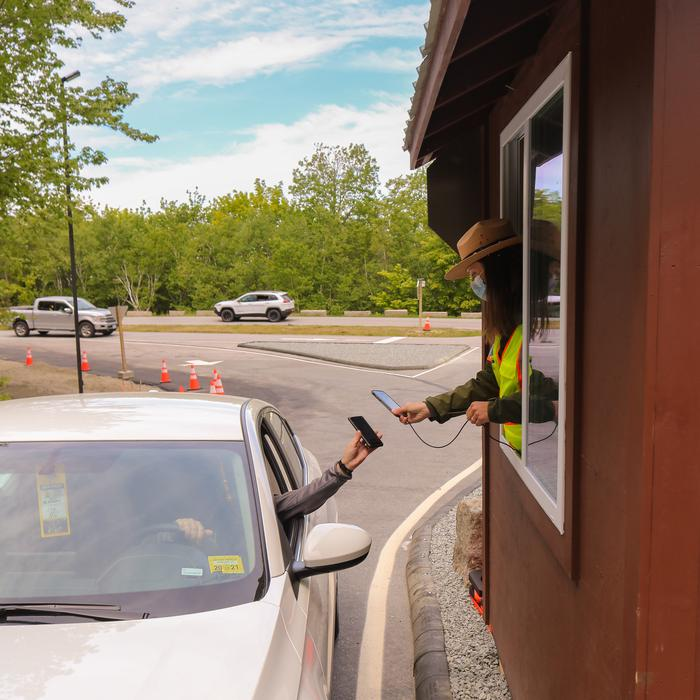 Park ranger leaning out of the window of an entrance booth to scan a digital vehicle reservation ticket on the phone of a driver in a white car.Park ranger scans digital QR code to validate vehicle reservation.
