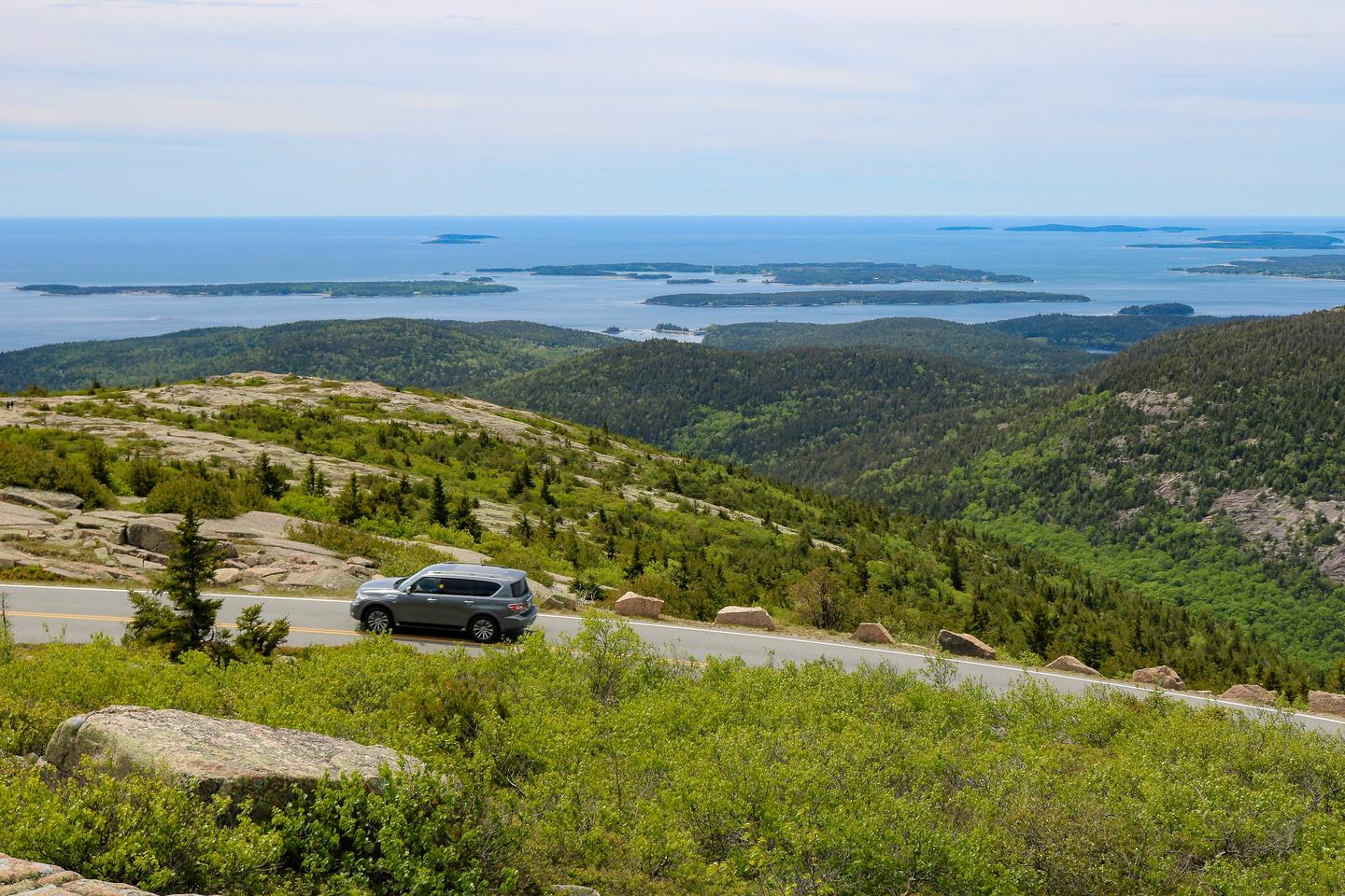 A car travels along a narrow mountain road lined by large stones across the view in the foreground with a forested valley, coastal islands, and the ocean in the background.Ascending Cadillac Summit Road with views to the south of the Maine coast.