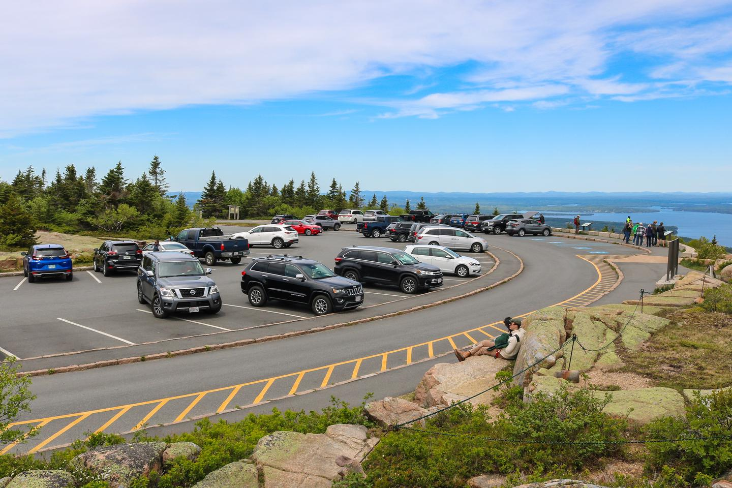 About 25 cars parked in a crescent shaped lot on top of a mountain with a distant view of the ocean and mountains in the background.Parking at the Cadillac Summit.