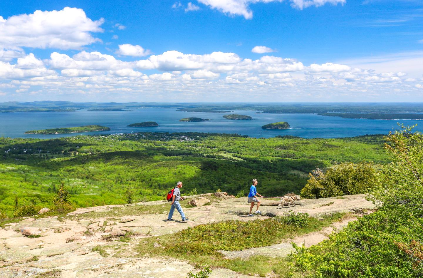 A man wearing a red daypack follows a woman with a golden retriever on a leash hiking from left to right across a granite outcrop in the foreground with forested hills below in the mid-ground and coastal islands dotting the ocean and billowy clouds above in the distant background.Hikers ascending Cadillac Mountain on the Cadillac North Ridge Trail with views of the Porcupine Islands and Frenchman Bay beyond.