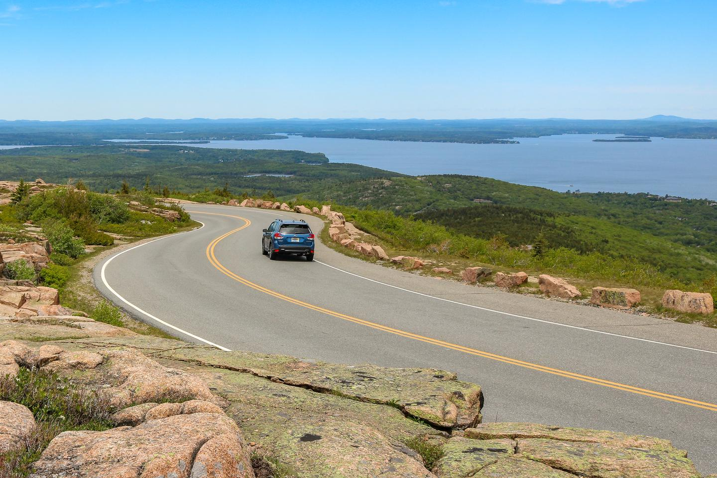 A car travels down a sinuous mountain road lined by large stones with a view to the right of the ocean and distant mountains in the background.Descending Cadillac Summit Road with views to the north of Frenchman Bay.