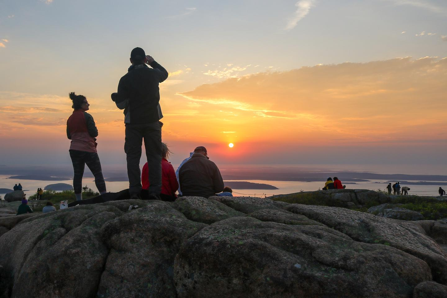 About a dozen people sitting and standing across granite outcrops watch the bright orange and red sunrise on the horizon overlooking the ocean from a mountain top.Sunrise on Cadillac Mountain.