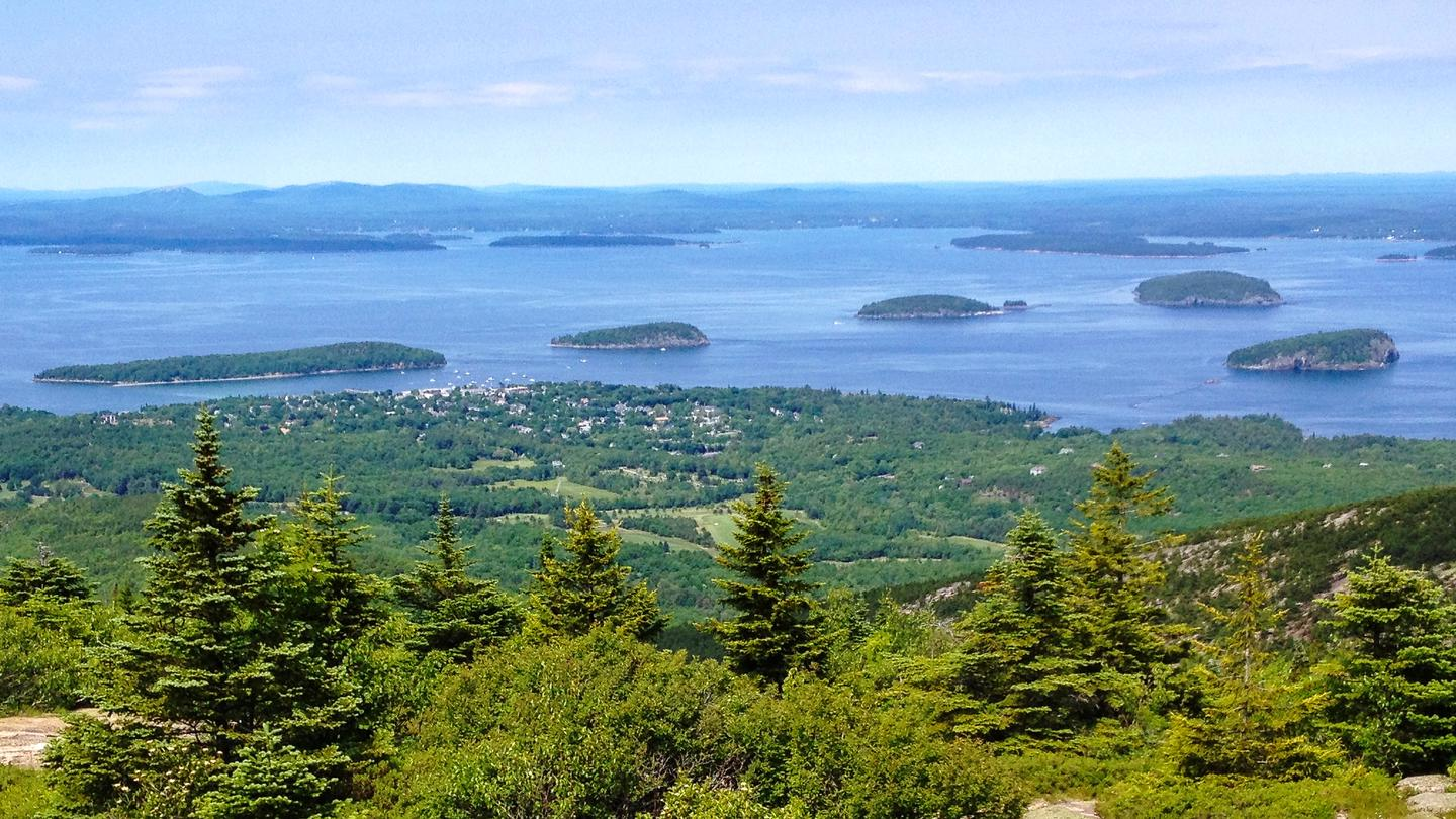 Sweeping view from Cadillac Summit across a forested slope and island-spotted bay to distance hills.Porcupine Islands and Frenchman Bay from Cadillac Mountain.