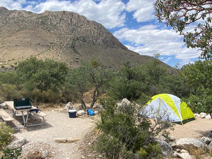 Tent campsite 19.  This view shows a picnic table to the left & tent pad, with 2 person tent displayed, to the right side of the site. Hunter Peak is visible in the background.Tent campsite 19 with picnic table and displaying a 2 person tent on the tent pad.