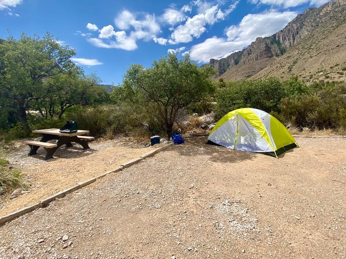 Tent campsite 20 has a large tent pad shown here with a two person tent and a picnic table to the left of the site.  Small trees near the site may offer shade at times.Tent campsite 20 with a large tent pad and picnic table, mountain views in the background.