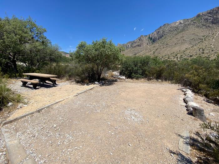 Overview of tent site 20. Tent pad is on the right when approached and the picnic table is to the left.  Desert vegetation offers some privacy but this site is at a road intersection.Campsite 20 shown with a picnic table and large size tent pad.