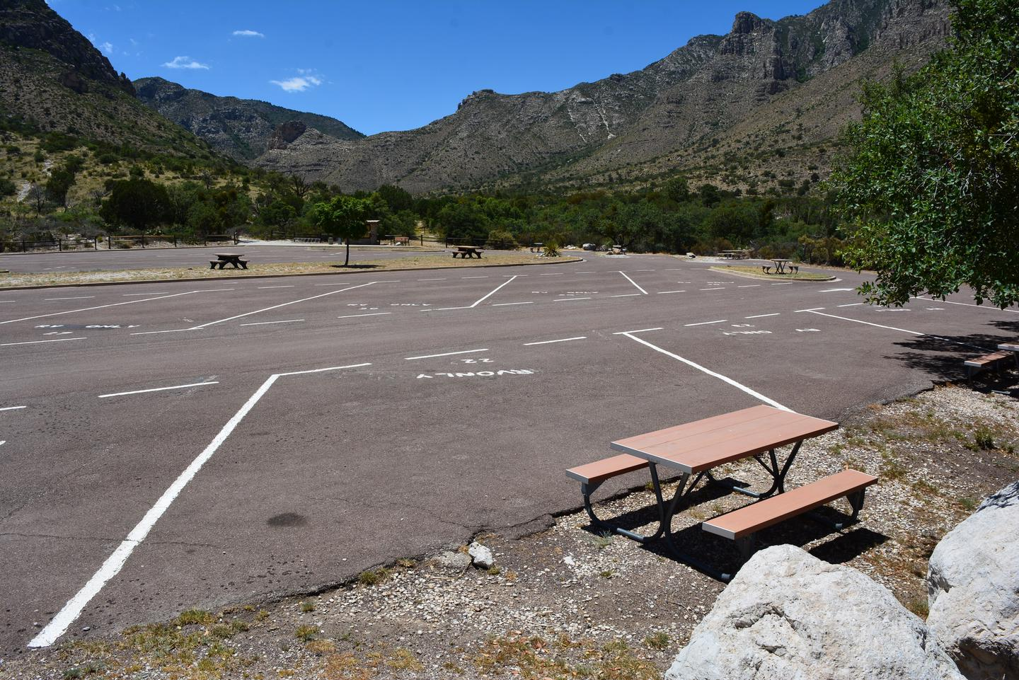 RV site 22 shown from the back edge of the site.  The picnic table is off the edge of the paved space.  Views of the Pine Spring Canyon visible across other campsites.RV campsite number 22 with views of the Pine Spring Canyon and surrounding mountains.