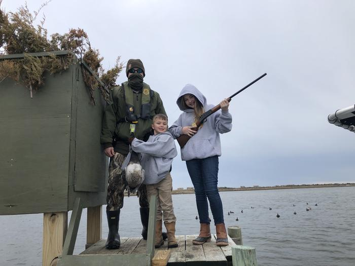 View of Park Ranger posing on a duck blind with a boy holding a duck and a girl with a shotgun on Youth Hunting DayView of a Park Ranger posing on a duck blind with two children.  A boy is holding a red headed duck and the girl is holding a shotgun.  Youth Hunting Day.
