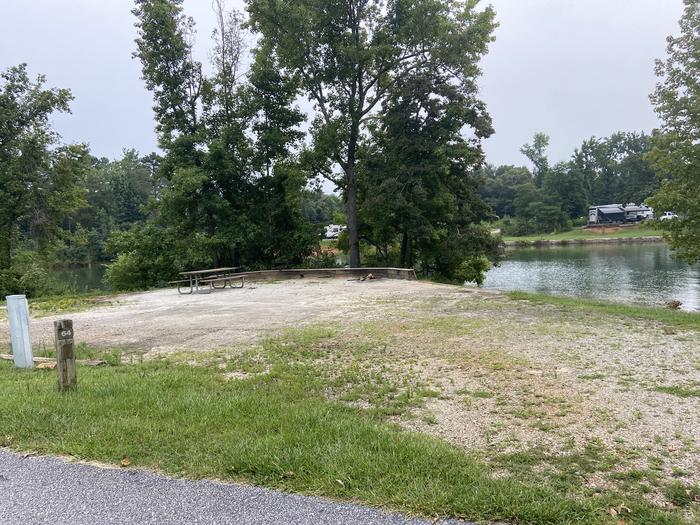 A photo of Site 64 of Loop SPRINGFIELD  at SPRINGFIELD with Picnic Table, Electricity Hookup, Fire Pit, Shade, Tent Pad, Waterfront, Lantern Pole, Water Hookup