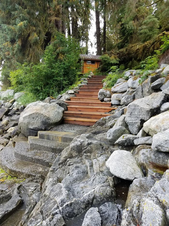 Stone and wooden steps leading up to an outhouse.Steps to the trailhead