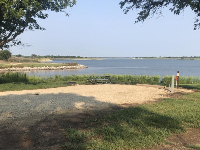 A photo of Site A-006 of Loop A at WEST ROLLING HILLS with Picnic Table, Electricity Hookup, Fire Pit, Shade, Waterfront, Water Hookup
