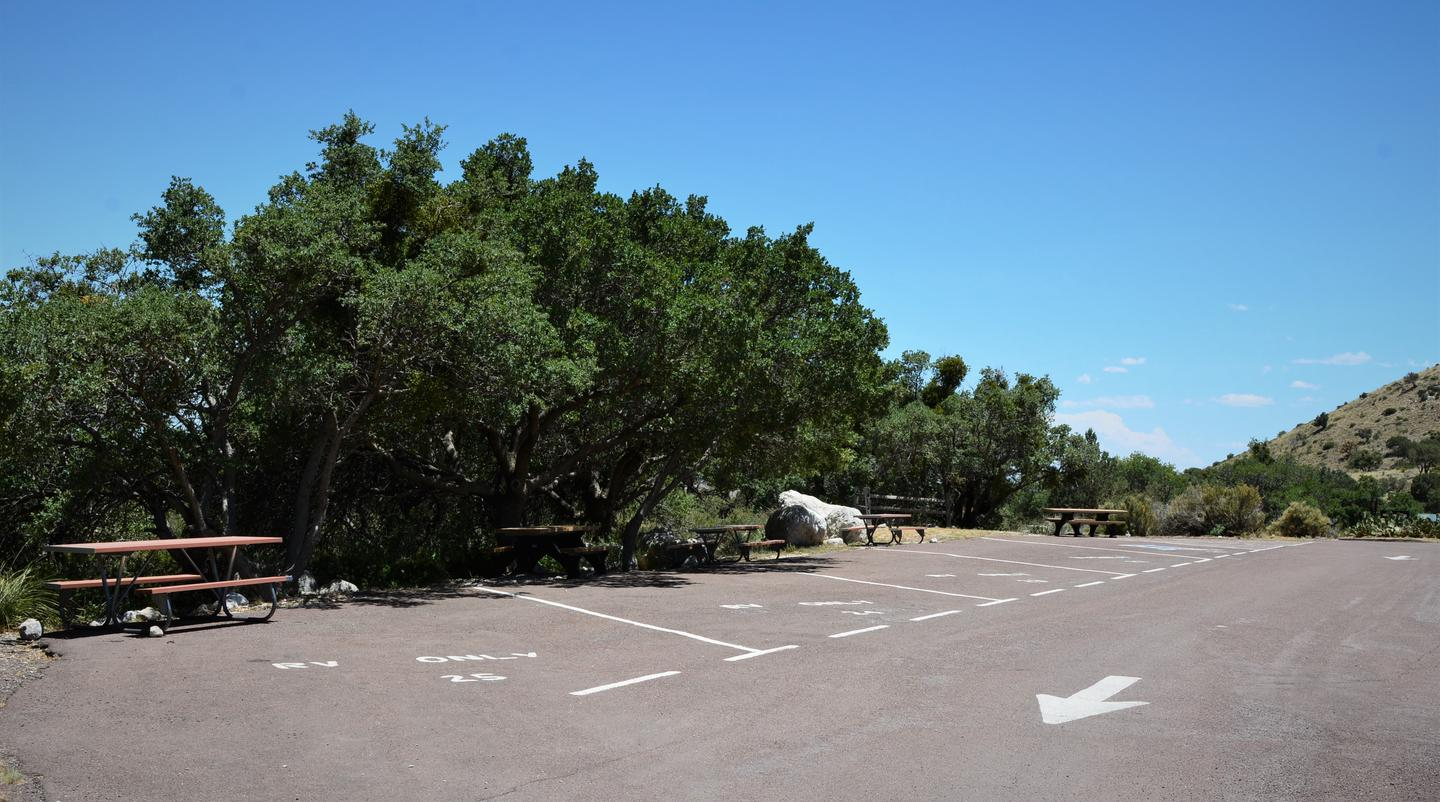 RV campsite 23 is the in the center of 5 other campsites, all sites are paved and delineated by painted markings.RV campsites 21-25.  Site 23 has a campsite on each side.