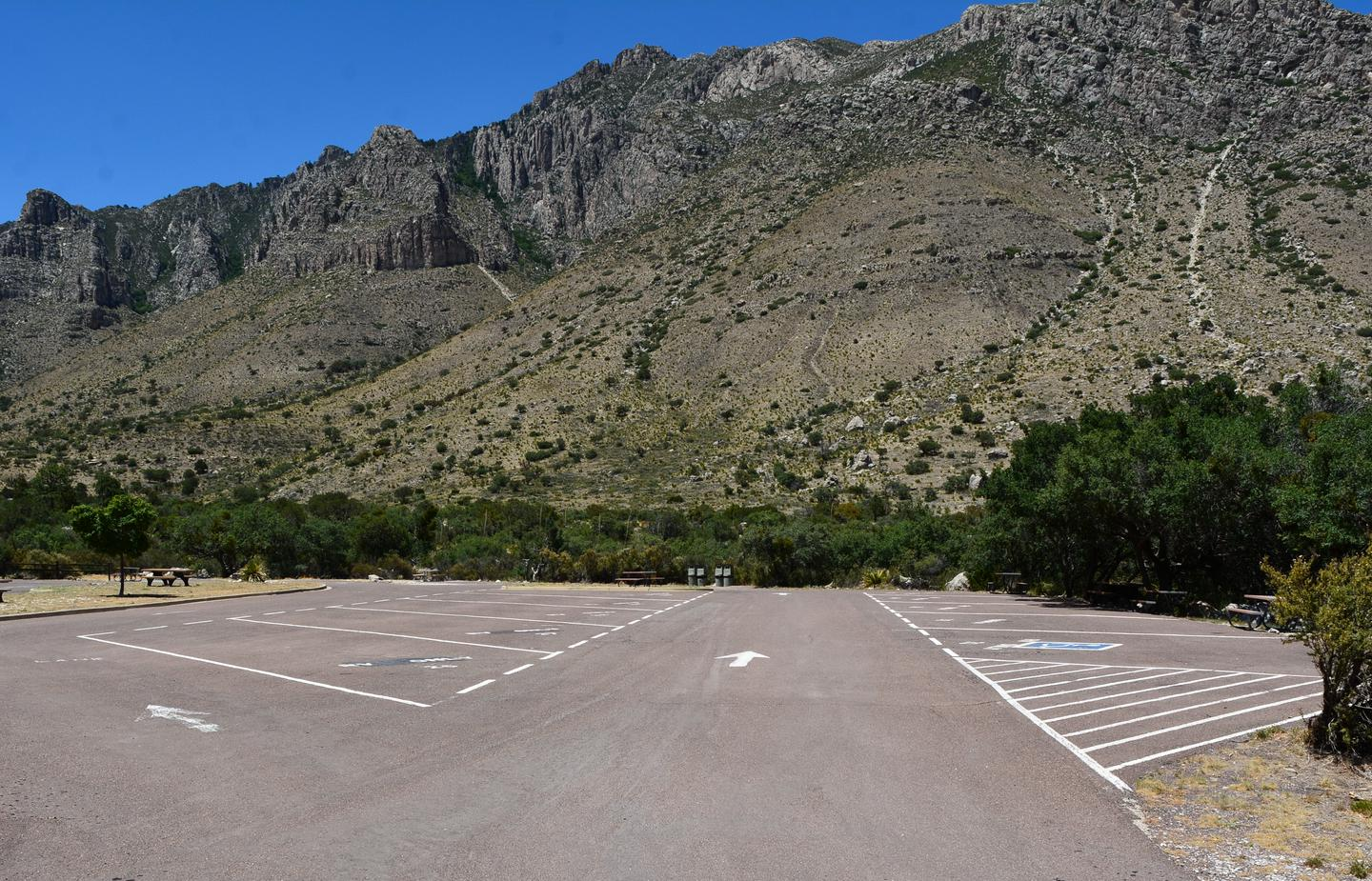 A view of RV campground parking area with sites 21-30 shown.  Site 24 is located along the right side of travel lane.  Mountain views in the background.A view of RV campground parking area with sites 21-30 shown.  Site 24 is located along the right side of travel lane.