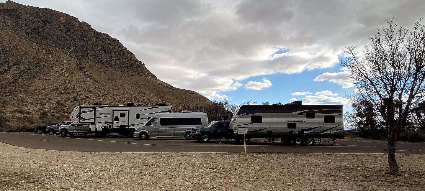 Row of RV campsites number 26-30.  The sites are occupied in this photo to help demonstrate the layout of the sites as a row of paved parking spaces.Row of RV campsites number 26-30.  Site 26 is the space nearest to the camera.